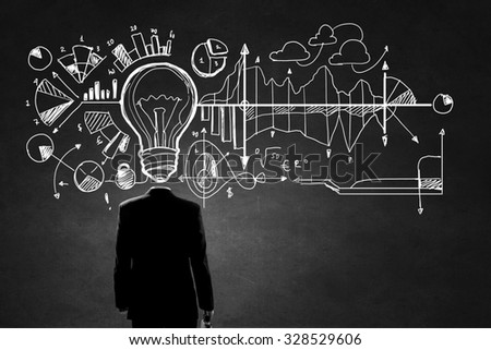 Unrecognizable businessman with business sketches instead of head on cement background - stock photo