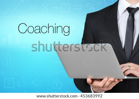 Unrecognizable businessman with laptop standing near text - coaching - stock photo