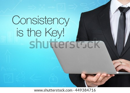Unrecognizable businessman with laptop standing near text - consistency is the key! - stock photo