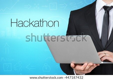 Unrecognizable businessman with laptop standing near text 'hackathon' - stock photo