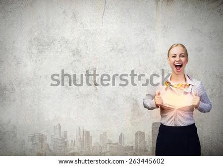 Unrecognizable businesswoman opening her shirt like superhero - stock photo