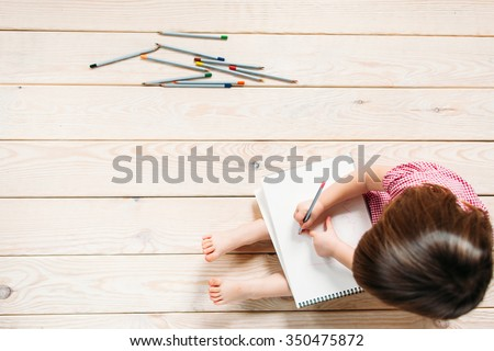 Unrecognizable child learns to draw with colored pencils. Girl sitting on the wooden floor and draw simple drawings. - stock photo