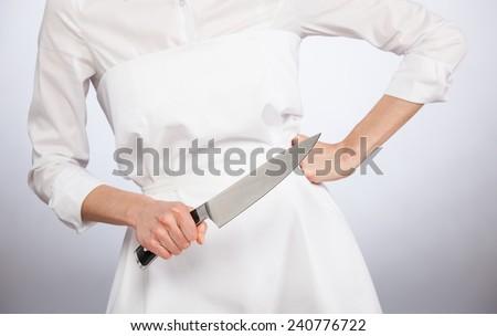 Unrecognizable cook holding a big kitchen knife - closeup shot - stock photo