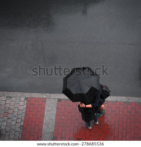 unrecognizable couple of people under an umbrella view from the top - stock photo