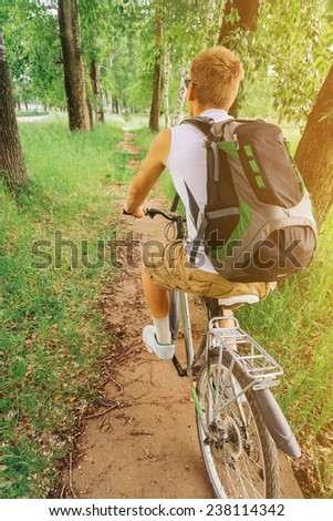 Unrecognizable cyclist man riding mountain bike on trail in summer forest, rear view. Theme of sport and hiking - stock photo