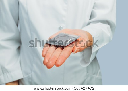 Unrecognizable doctor gives condom, concept of safe sex - stock photo
