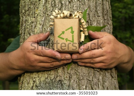 Unrecognizable Environmentalist person holding gift with recycling symbol in front of tree bark and leaf - stock photo