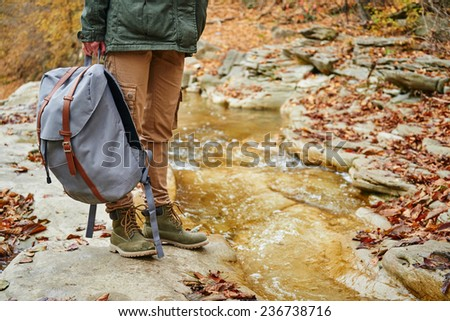 Unrecognizable female hiker with backpack standing near a stream in autumn forest, view of legs. Focus on backpack