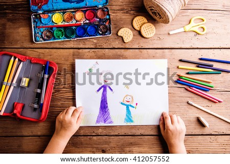 Unrecognizable girl drawing picture of her and her mother - stock photo