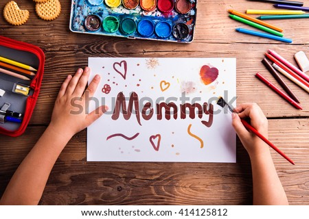 Unrecognizable girl painting picture for her mom, Mothers day - stock photo