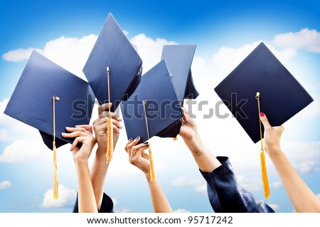 Unrecognizable group of people throwing graduations hats in the air - stock photo