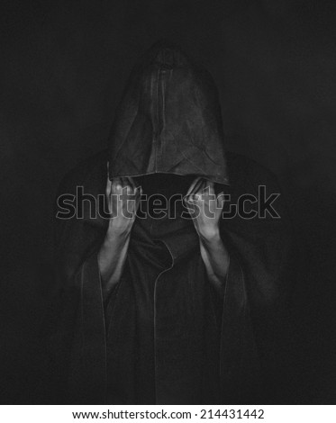Unrecognizable human in black coat with a hood, face is not visible. monochrome image. Image with low contrast and film grain - stock photo