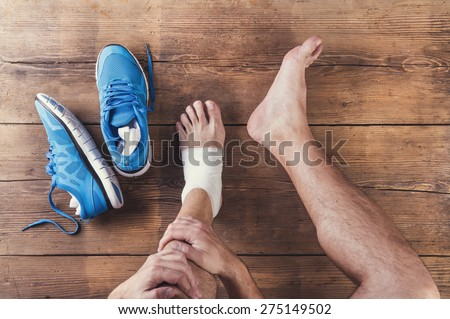 Unrecognizable injured runner sitting on a wooden floor background - stock photo