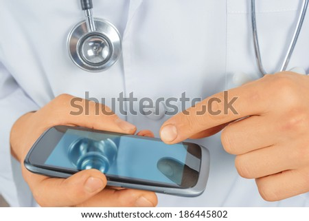Unrecognizable man doctor is touching on mobile phone, close-up - stock photo