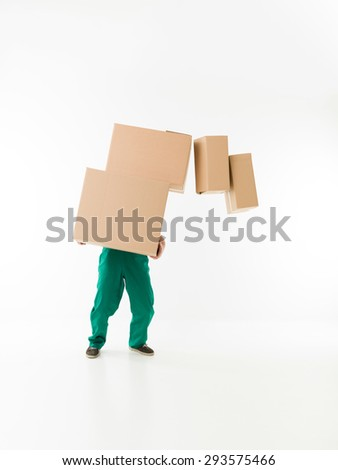 unrecognizable man holding stack of cardboard boxes, dropping some of them - stock photo