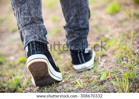 Unrecognizable man in rubber shoes stepping on footpath, rear view, close-up - stock photo