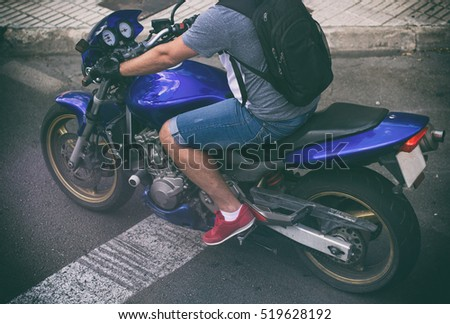 Unrecognizable man on motorcycle in the street.