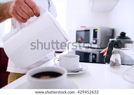 Unrecognizable man preparing coffee. Pouring water into a cup. - stock photo