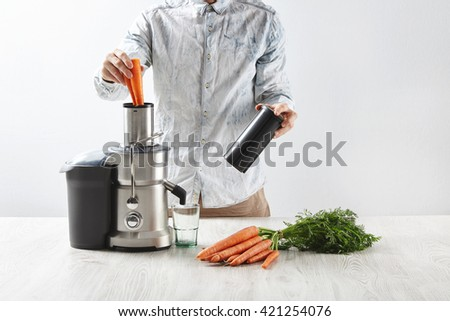 Unrecognizable man puts carrots inside metallic professional juicer with empty glass to make tasty juice for breakfast, fresh carrots lying on wooden table. Isolated on white background in cafe shop - stock photo