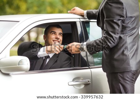 Unrecognizable man standing in front of the car and paying to a taxi driver - stock photo