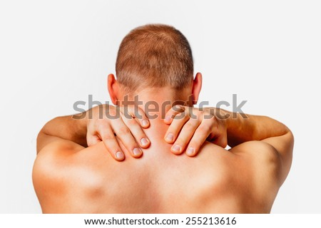 Unrecognizable man touches his neck, pain in the neck, rear view, on a white background