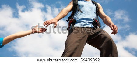 unrecognizable muscular man reaches out to female hand on a background of a beautiful sky - stock photo