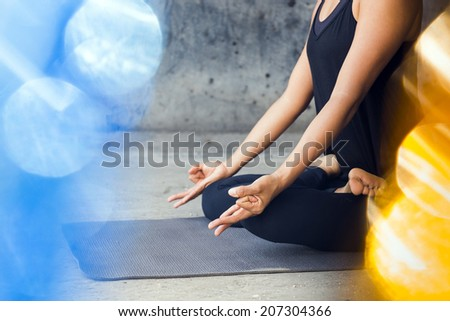 Unrecognizable oman in lotus practicing meditation with a colorful background - stock photo