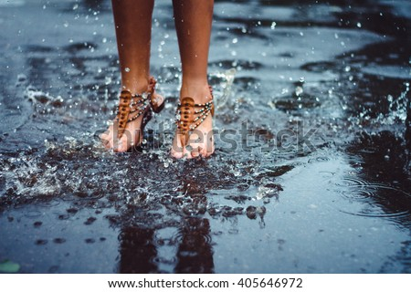 Unrecognizable person (female) is splashing water in a puddle on a rainy day in the city. Legs in puddle. - stock photo