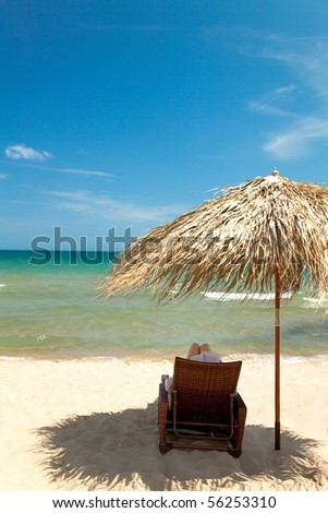 Unrecognizable person reading book in canvas chair on beautiful tropical beach - stock photo