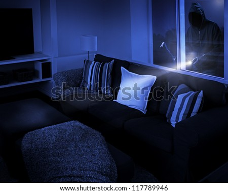 Unrecognizable person with flashlight and crowbar looking through living room window. - stock photo
