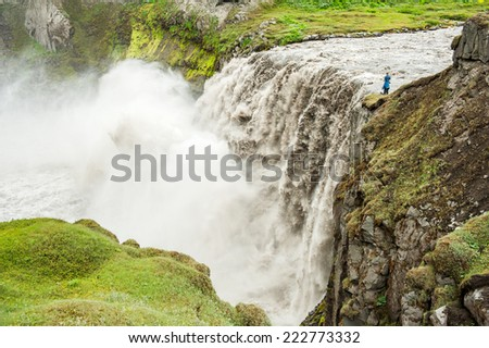 Unrecognizable photographer is taking pictures of Hafragilsfoss, very powerful waterfall. It is located in Jokulsargljufur National Park the northeasten Iceland on the river Jokulsa a Fjollum.  - stock photo