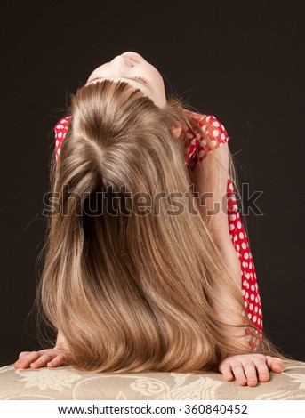 Unrecognizable portrait of a little girl with beautiful long hair, black background - stock photo