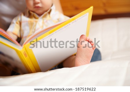 Unrecognizable reading baby with book - stock photo