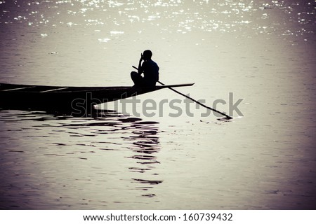 Unrecognizable silhouette of a young black boy sitting on his small vessel on the Niger River in Mali, 2010. - stock photo