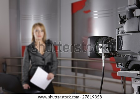 unrecognizable television news reporter in front of the video camera in studio in live transmission - stock photo