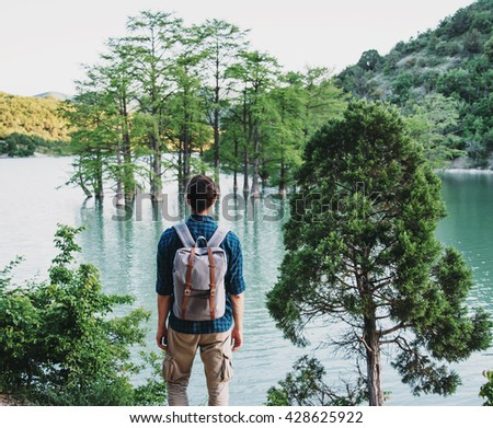 Unrecognizable traveler young man with backpack standing on coast of lake and enjoying view of nature, rear view - stock photo
