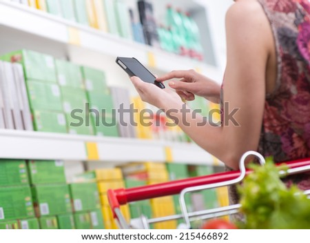 Unrecognizable woman at store using smartphone with shelves on background. - stock photo