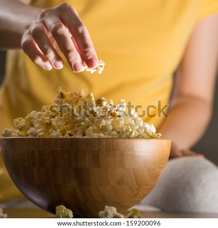 Unrecognizable woman eating popcorn at the cinema. Banner with copyspace - stock photo