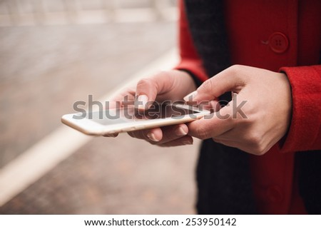 Unrecognizable woman in the city street texting with her smart phone - stock photo