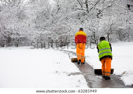 Unrecognizable workers removing first snow from pavement in park - stock photo