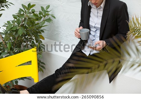 unrecognizable young business woman using her smartphone outdoors and relaxing - stock photo