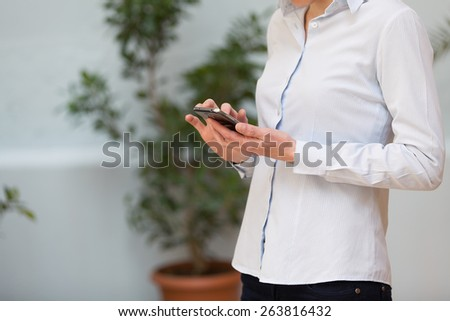 unrecognizable young business woman using her smartphone outdoors and relaxing.shallow depth of field with focus on the hand - stock photo