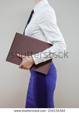 Unrecognizable young businesswoman going away, rear view; neutral background - stock photo