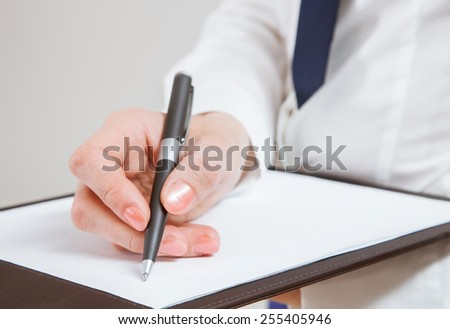 Unrecognizable young businesswoman  holding documents and a pen, neutral background - stock photo