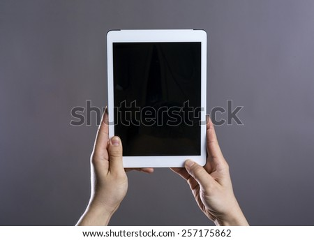 Unrecognizable young hipster with his tablet. Studio shot on gray background.