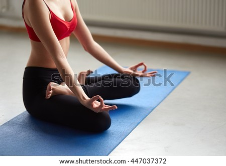 Unrecognizable young woman does yoga on mat indoors. Cropped portrait of girl sitting in seated cross legged pose relaxing in zen. - stock photo