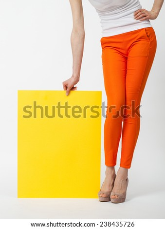 Unrecognizable young woman in orange pants holding blank yellow paper, closeup shot - stock photo