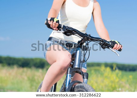 Unrecognizable young woman in shorts riding bicycle outdoors