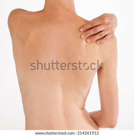 Unrecognizable young woman massaging her shoulder, white background