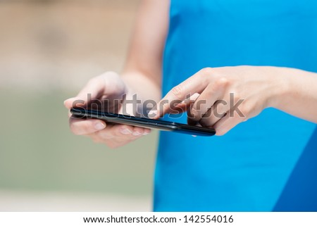 Unrecognized woman using touch screen smart phone in a close up shot - stock photo